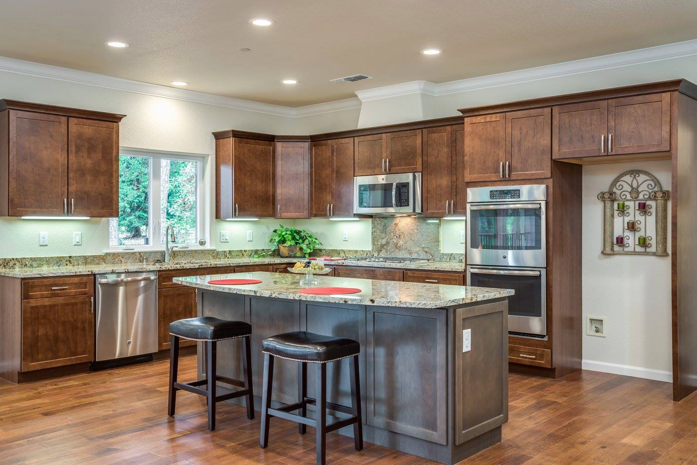 Kitchen with island, brown cabinets and marble counters