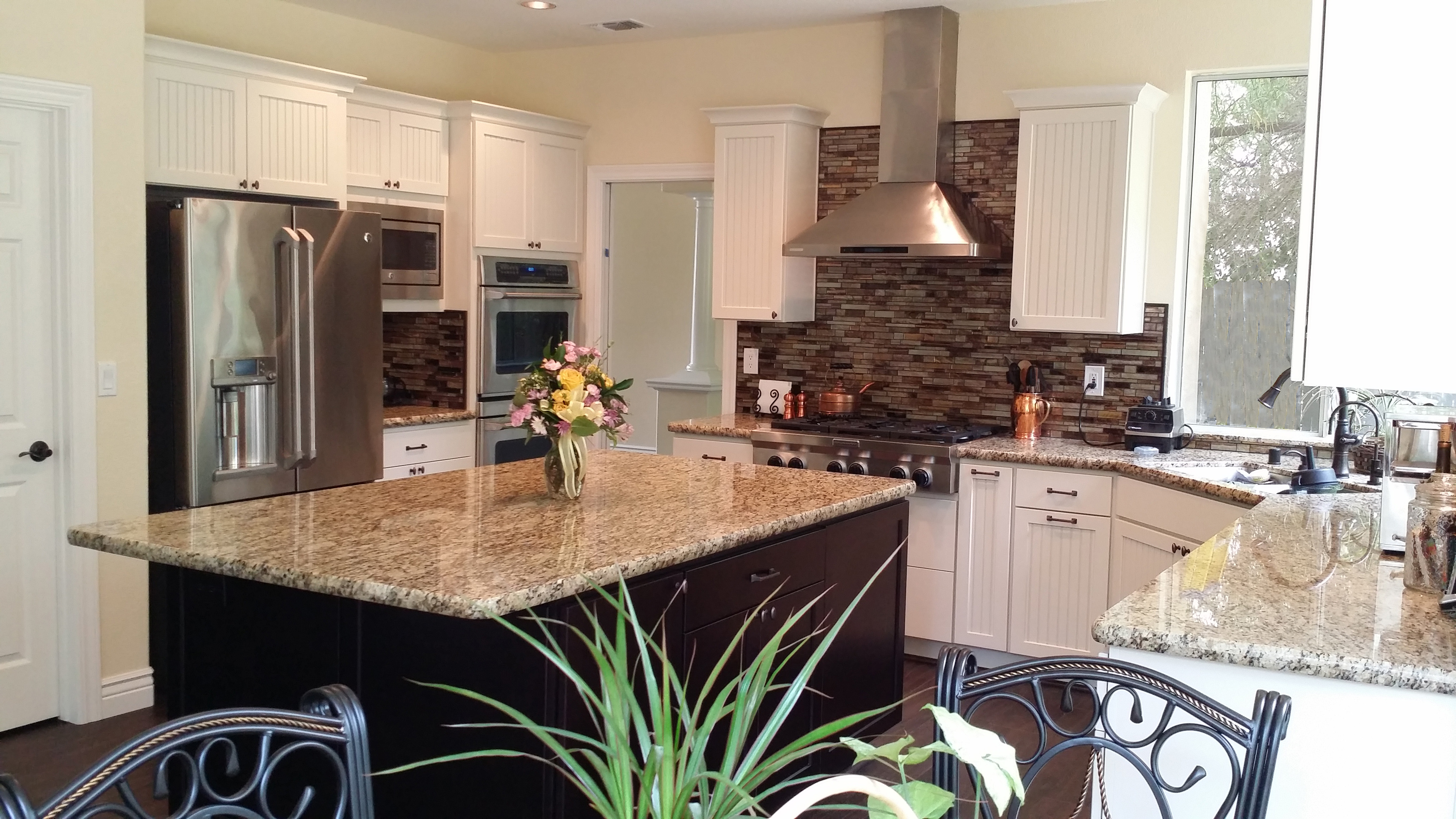 Black kitchen island with granite counter, white cabinets in background.