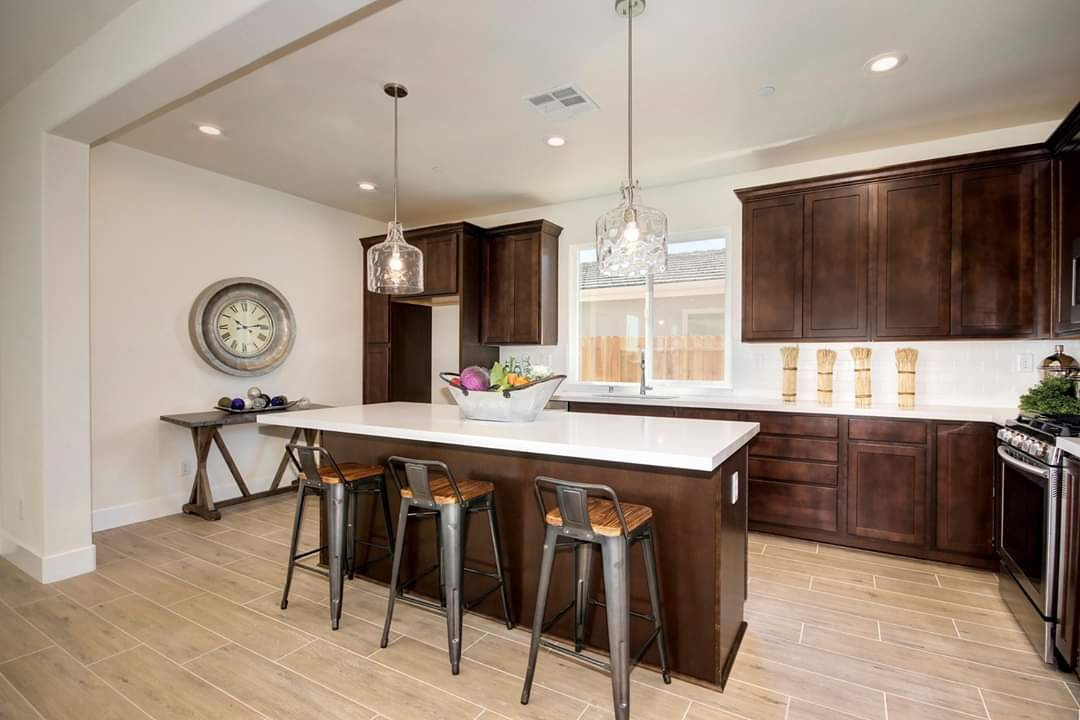 Kitchen bar with white counters and dark brown cabinets.