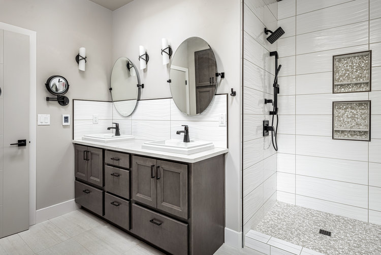 Light grey bathroom, darker grey vanity with white counters and oval mirrors.