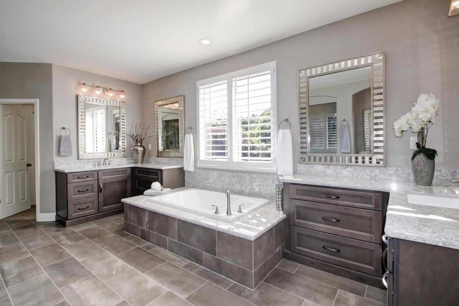 Master bath with tile bathtub, grey cabinet vanity and white counter