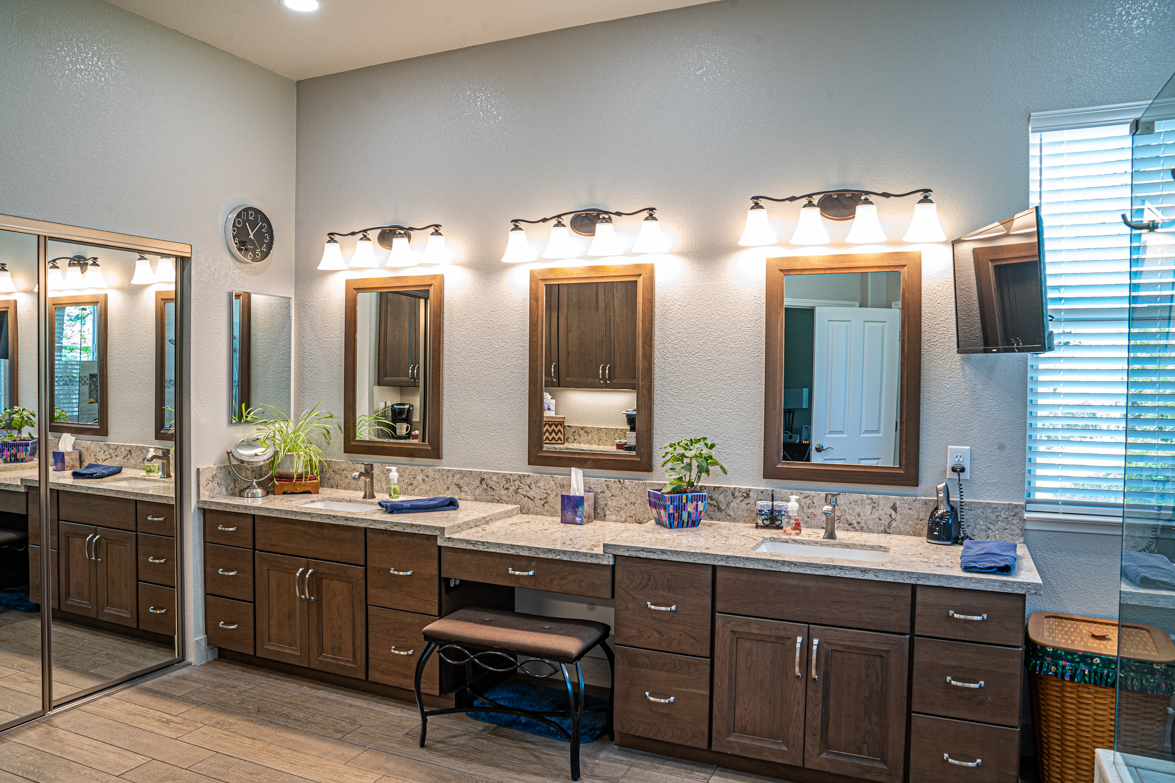 Bathroom vanity with dark cherry cabinets and tab marble counter.