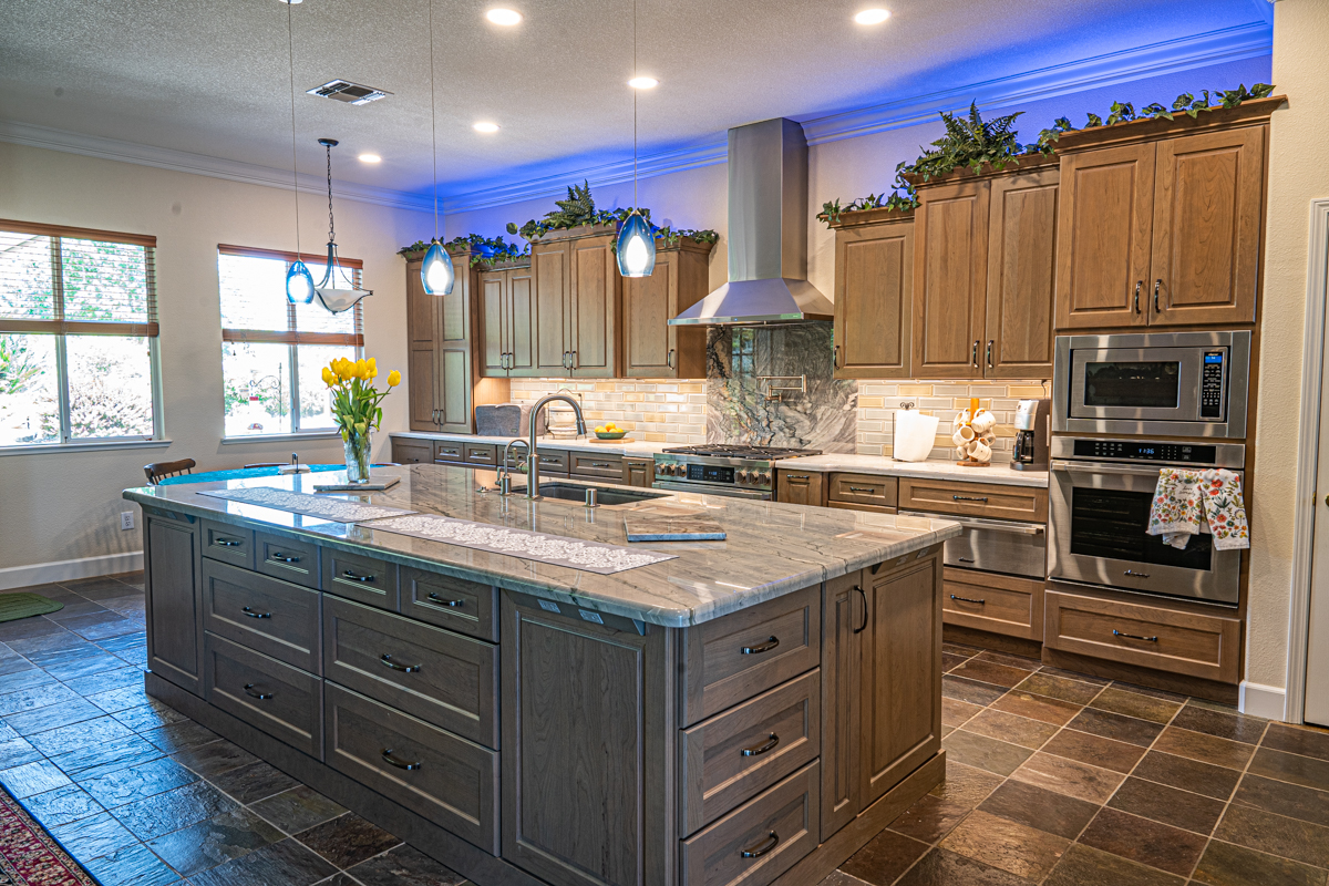 Kitchen with white kitchen island, light wooden cabinets and dark counters.