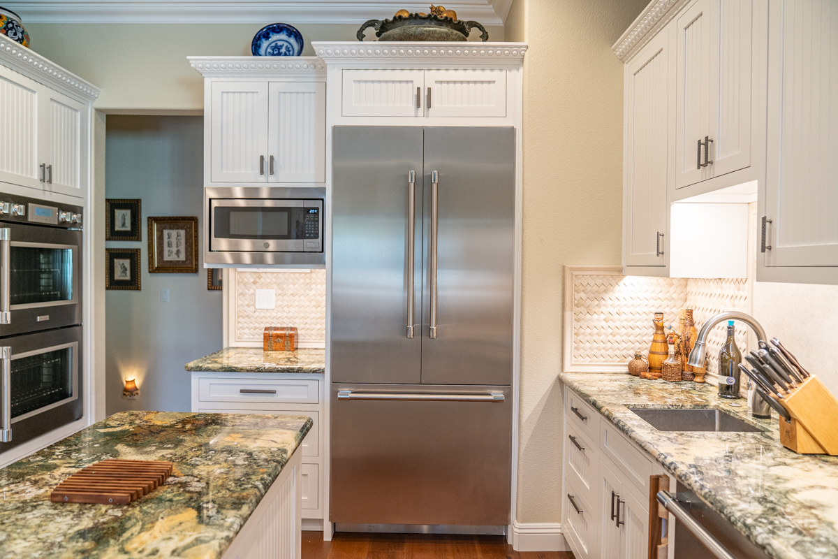 Traditional kitchen with white cabinets and grey marble counter tops