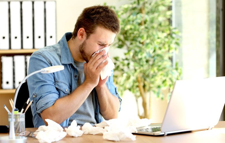 Man sitting on an office desk wiping his nose