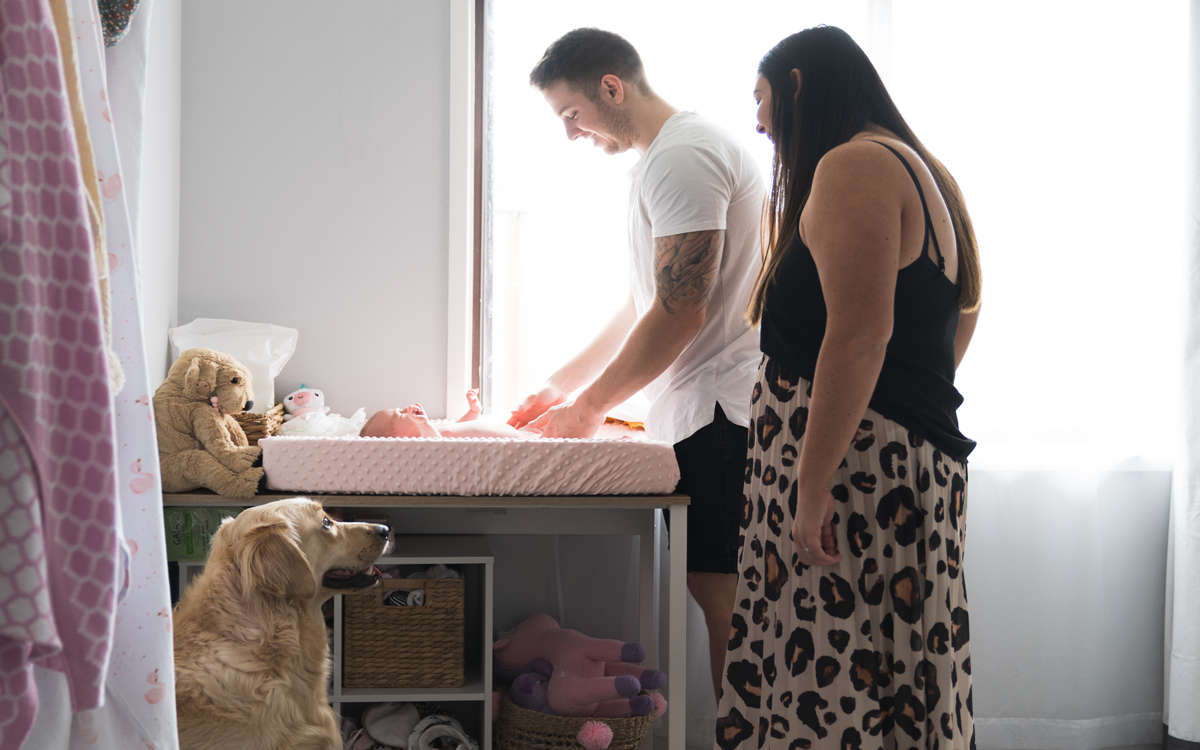 Parents changing baby with dog