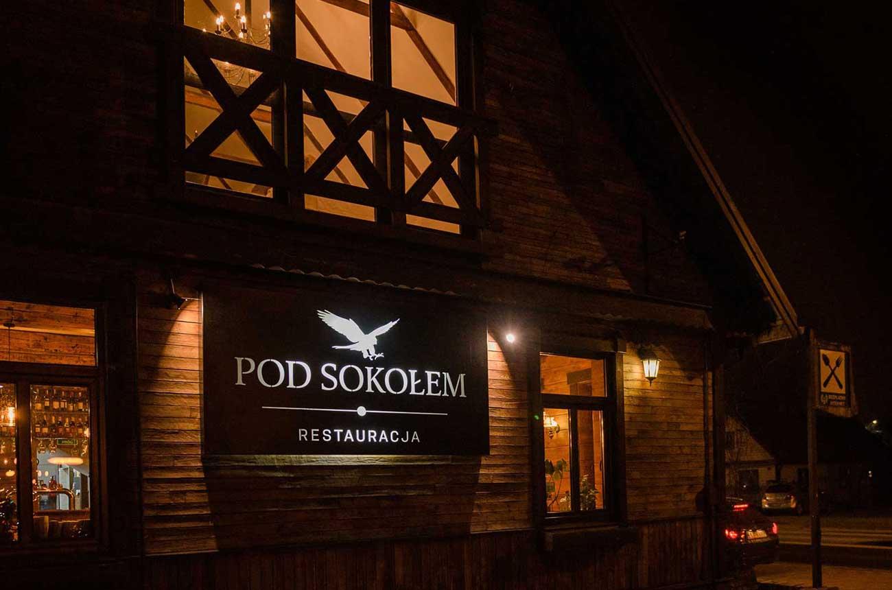 front restauracji pod sokołem wieczorem z podświetlonym logo