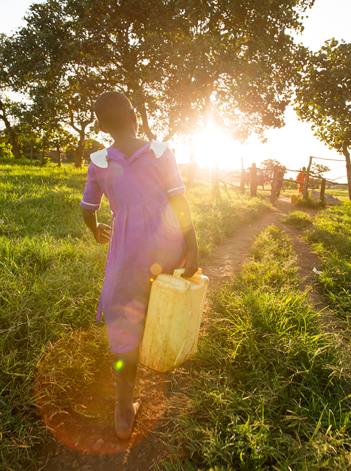 Girl carrying water canister walking towards the sunset.
