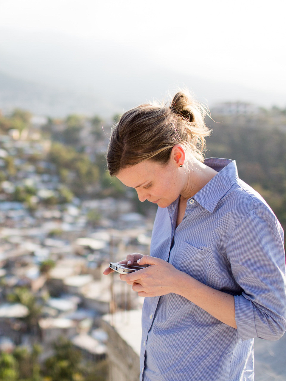 Photo of Becky Straw looking down and texting on a cellphone.
