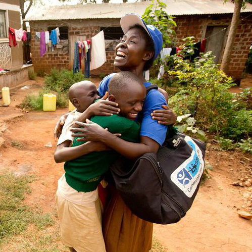 Living Goods community healthcare worker smiling while hugging two smiling children.