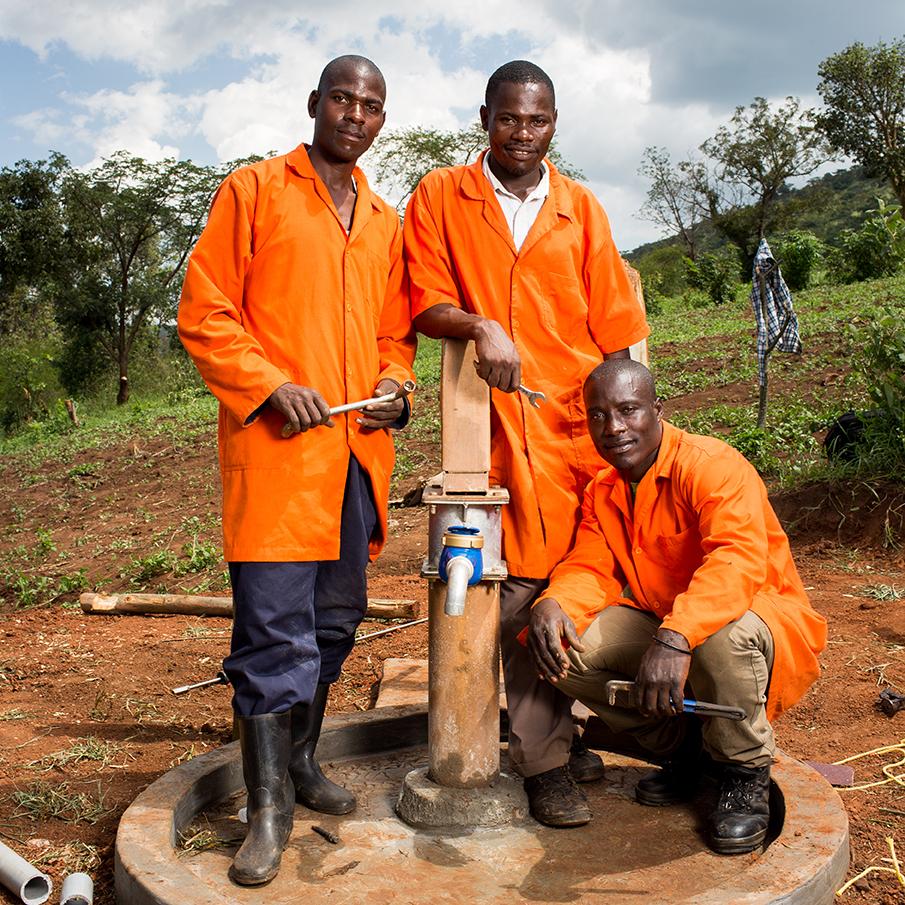 Three well mechanics holding tools while surrounding well pump.