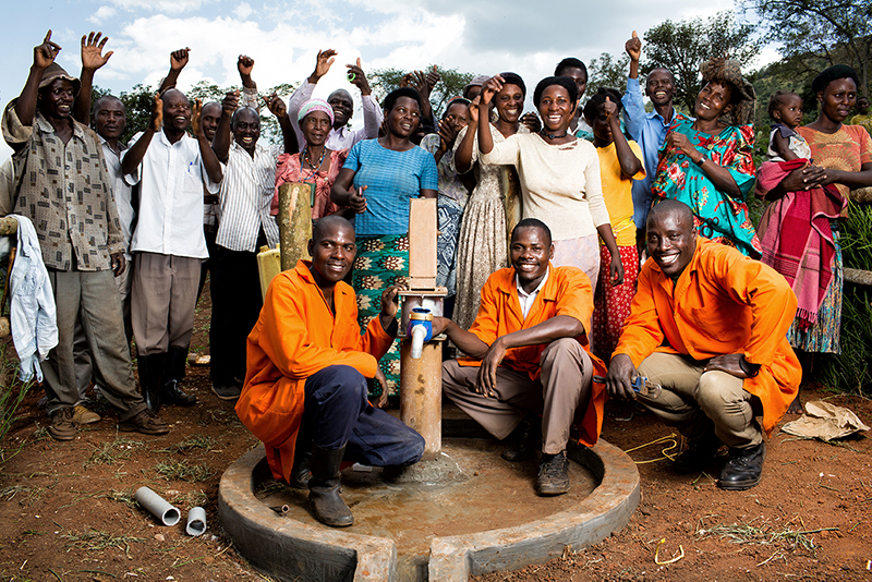 Community celebrating after fixing a well in Uganda.