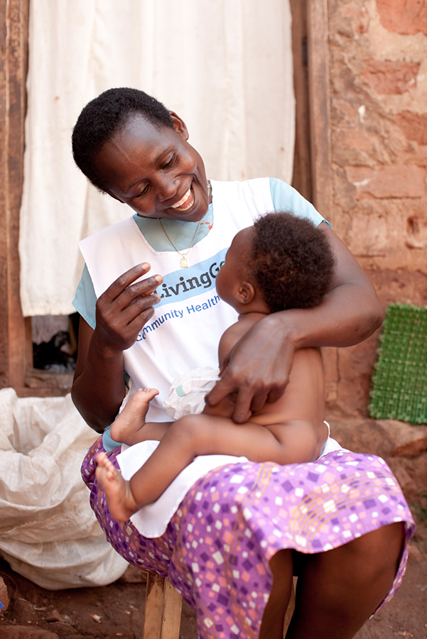 Living Goods Community Healthcare worker smiling at a baby sitting on her lap.