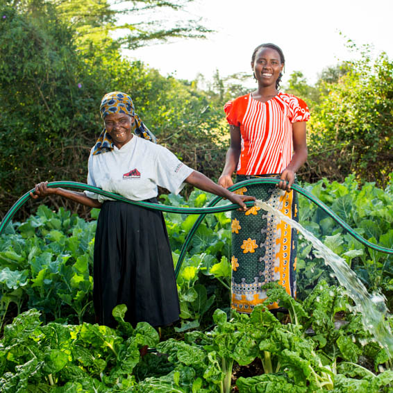 Two smiling women watering crops with hoses.
