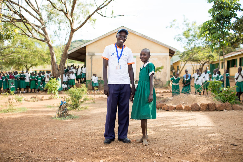 Community healthcare worker standing with girl in school uniform.