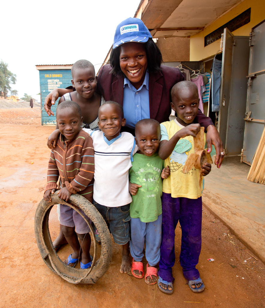 Living Goods worker smiling while among a group of smiling children.