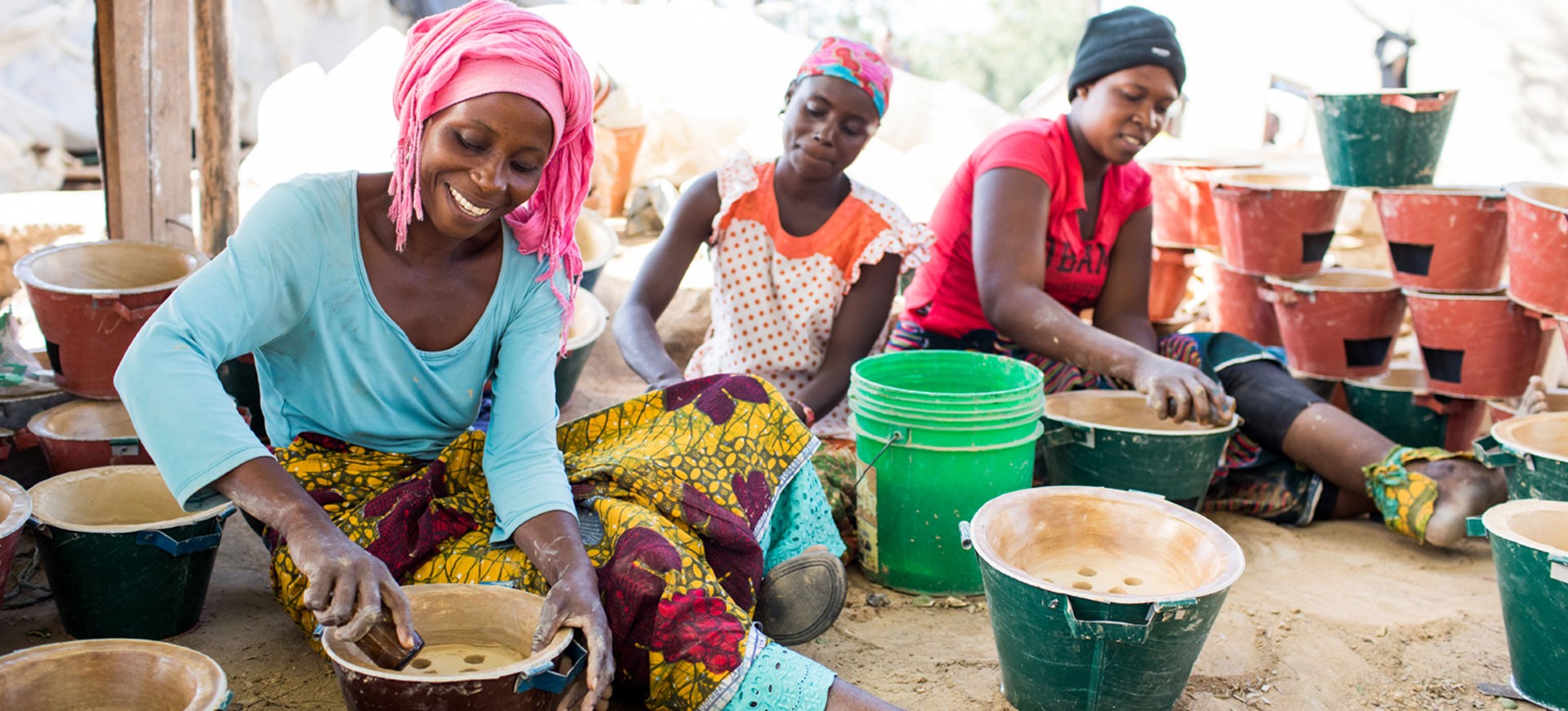 Three women smiling while making stoves.