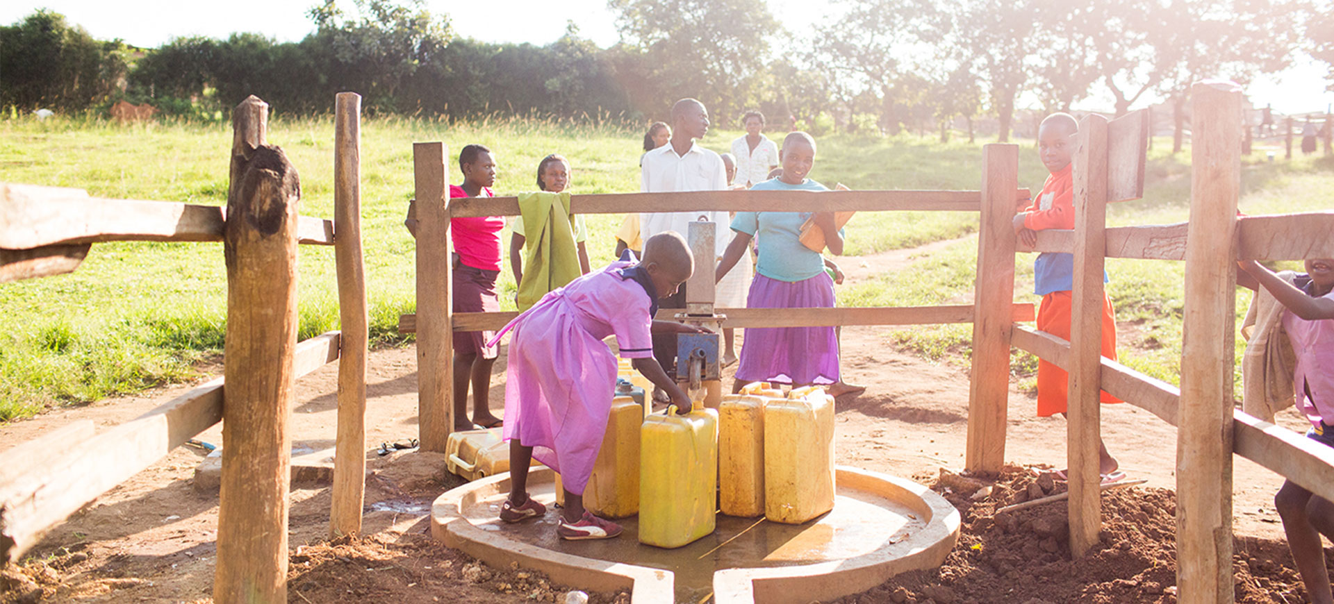 Young girl pumping water from well into water canister. Group of people in the background walking towards the well and standing on the fence surrounding the well.