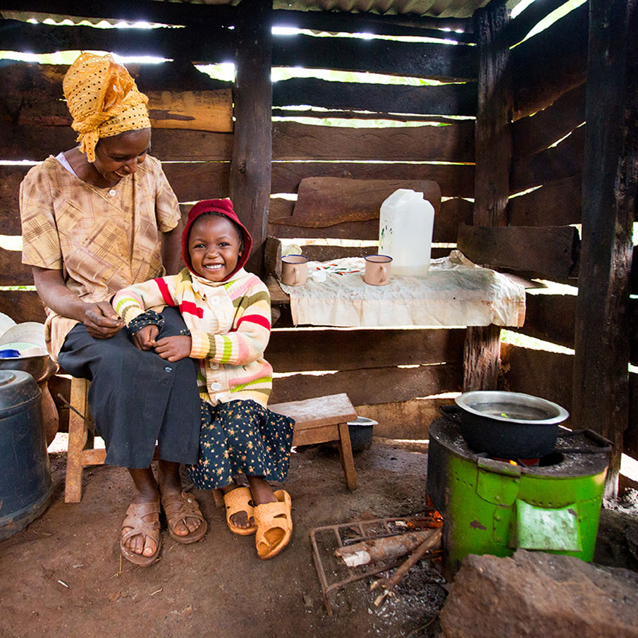 Mother sitting inside wooden house smiling down at smiling child leaning on her lap.