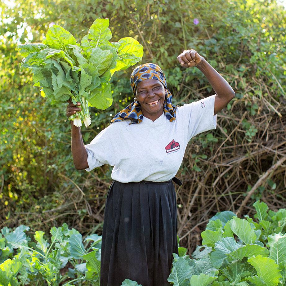A female farmer celebrates her harvest in Kenya.