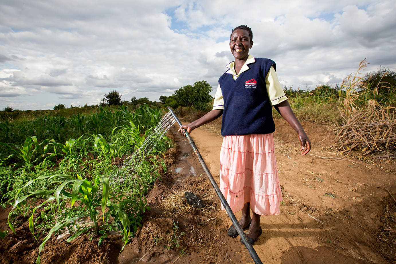 Women holding hose and watering crops while smiling.