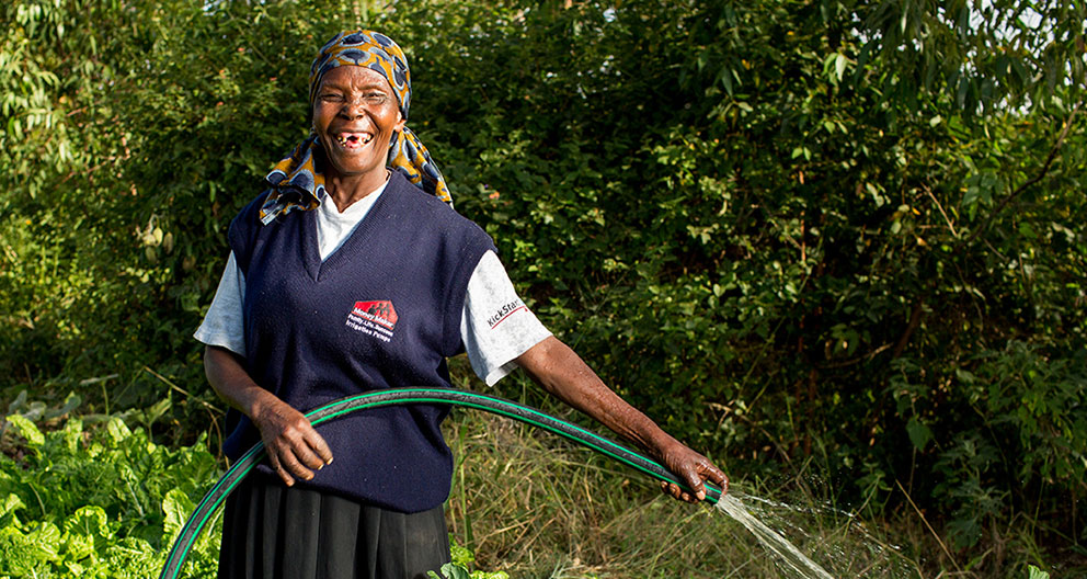 A female farmer in Kenya waters her crops.