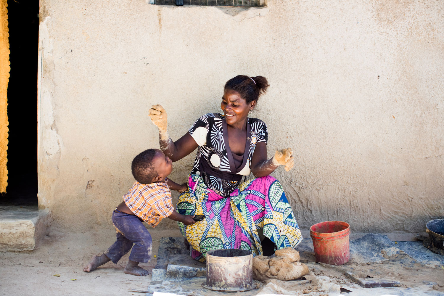 A mom in Tanzania takes a break from work to hug her toddler.