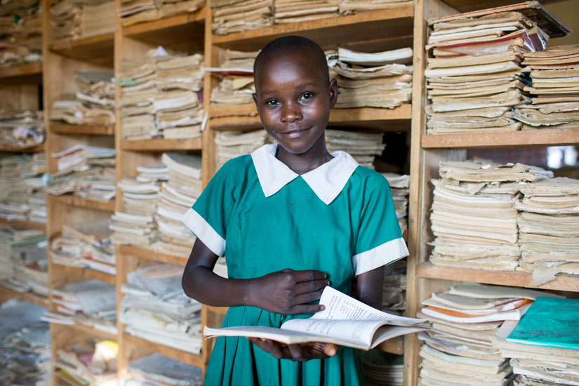 Girl in school uniform smiling while holding a book.
