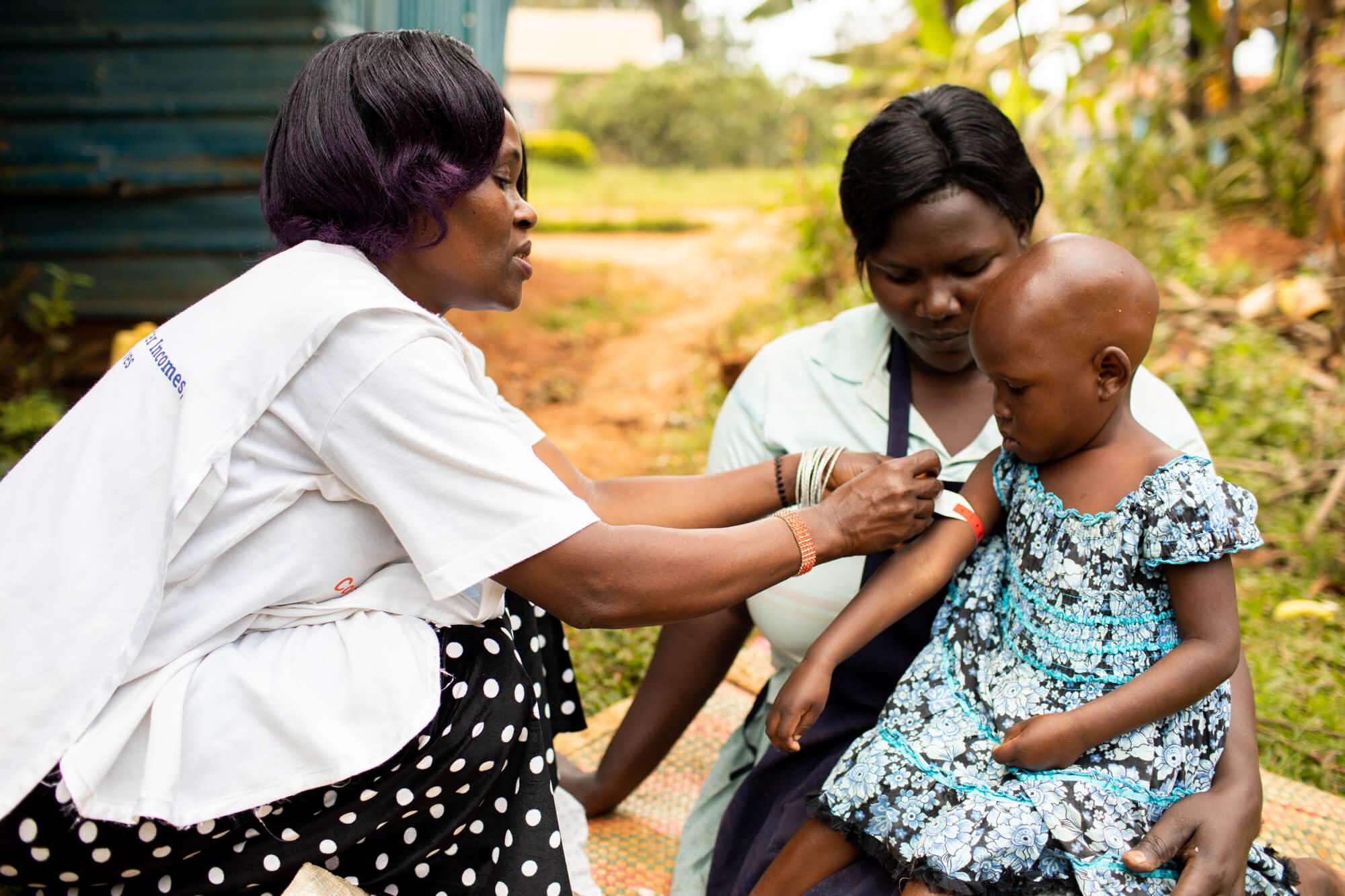 Christine checking child for malnutrition