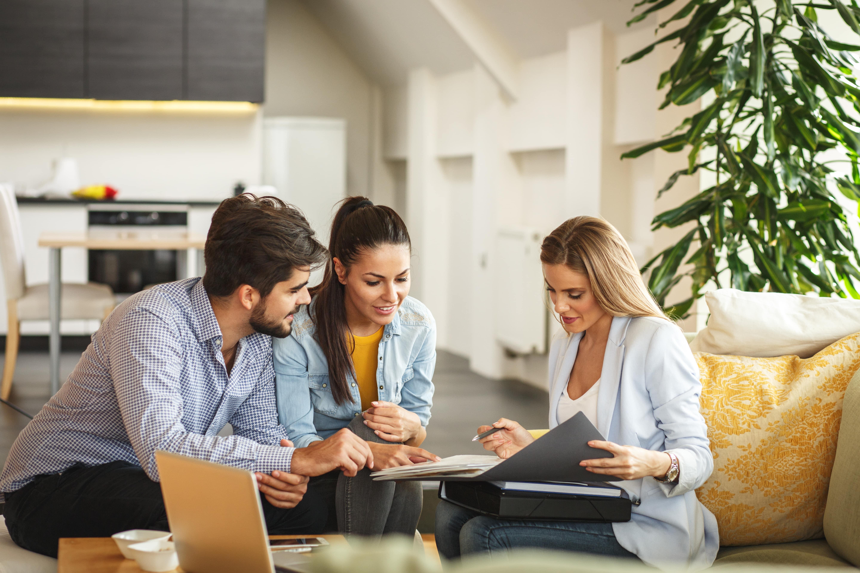 Agent immobilier faisant signer un bail de colocation à deux colocataires