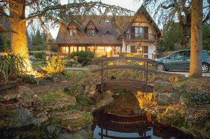 Maison dans la verdure avec un pont