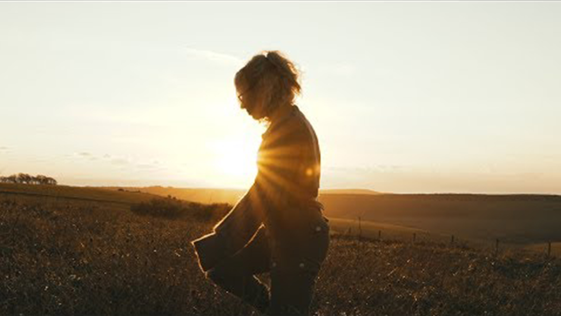 Girl Walking in a Field During Sunset