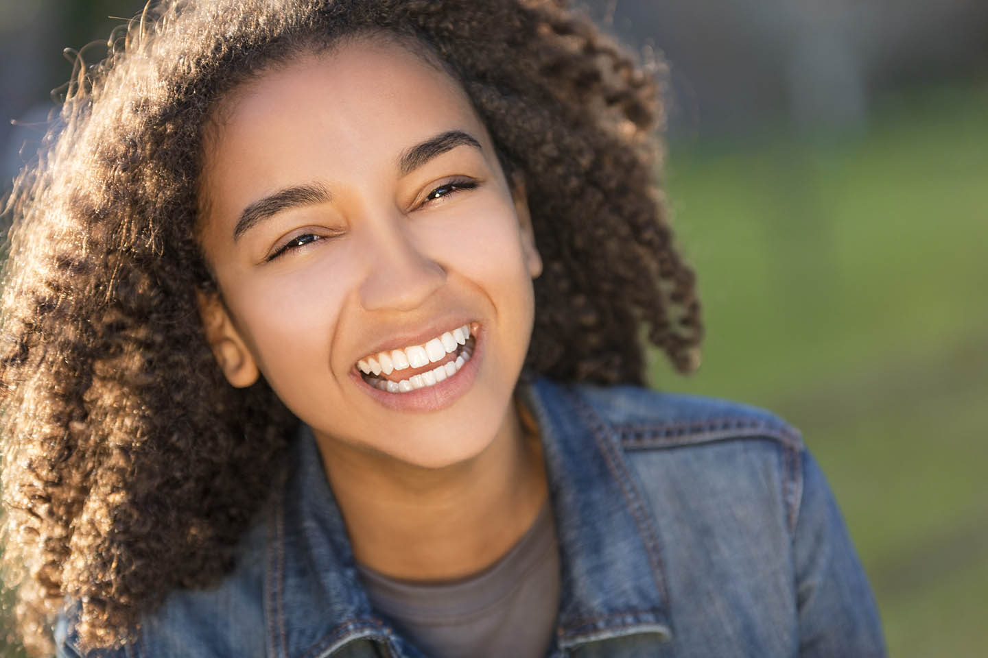 girl with jean jacket and curly hair smiling