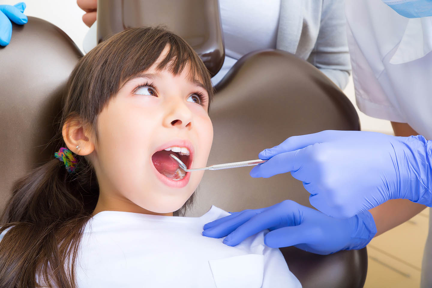 young girl getting teeth examined