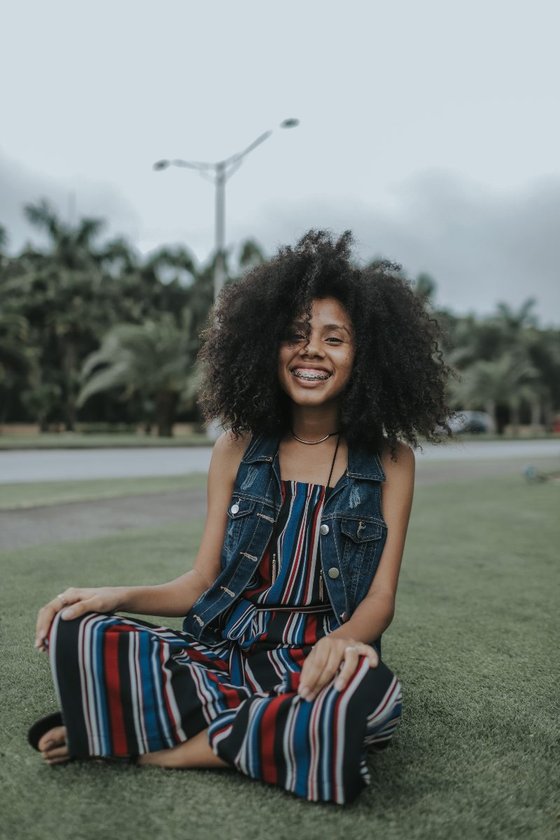 girl with curly hair and braces smiling