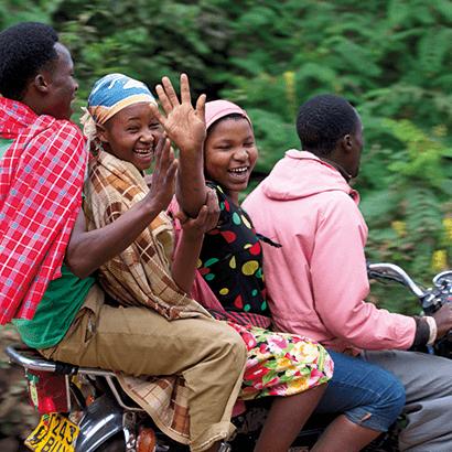 Vier lachende Afrikaner auf einem Roller