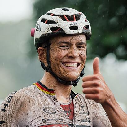 Mit Schlamm bespritzter Mountainbike-Fahrer lacht und zeigt Daumen nach oben