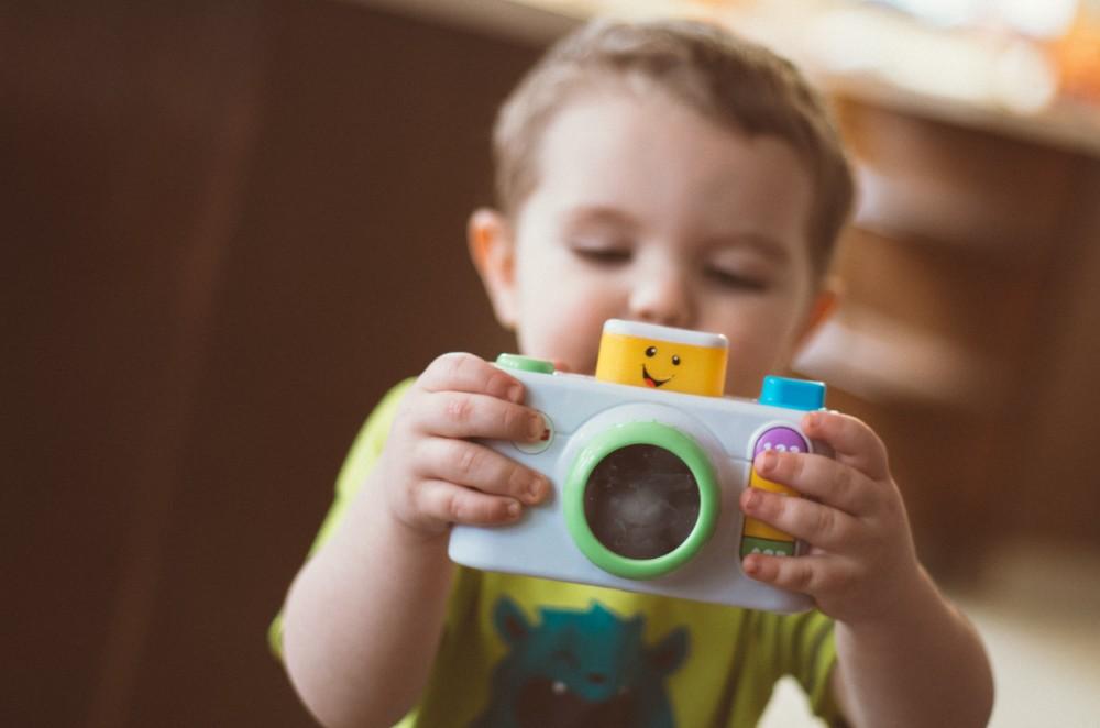 little boy holding a play camera