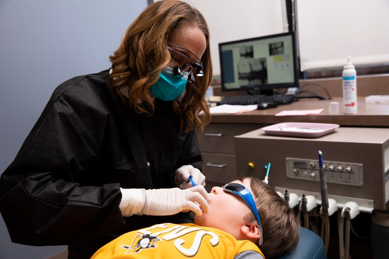 boy getting teeth examined while wearing sunglasses