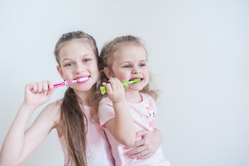 Two sisters brushing their teeth together