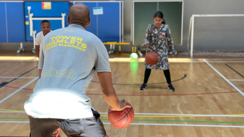 Tower Hamlets basketball team manager showing 2 students how to shoot hoops