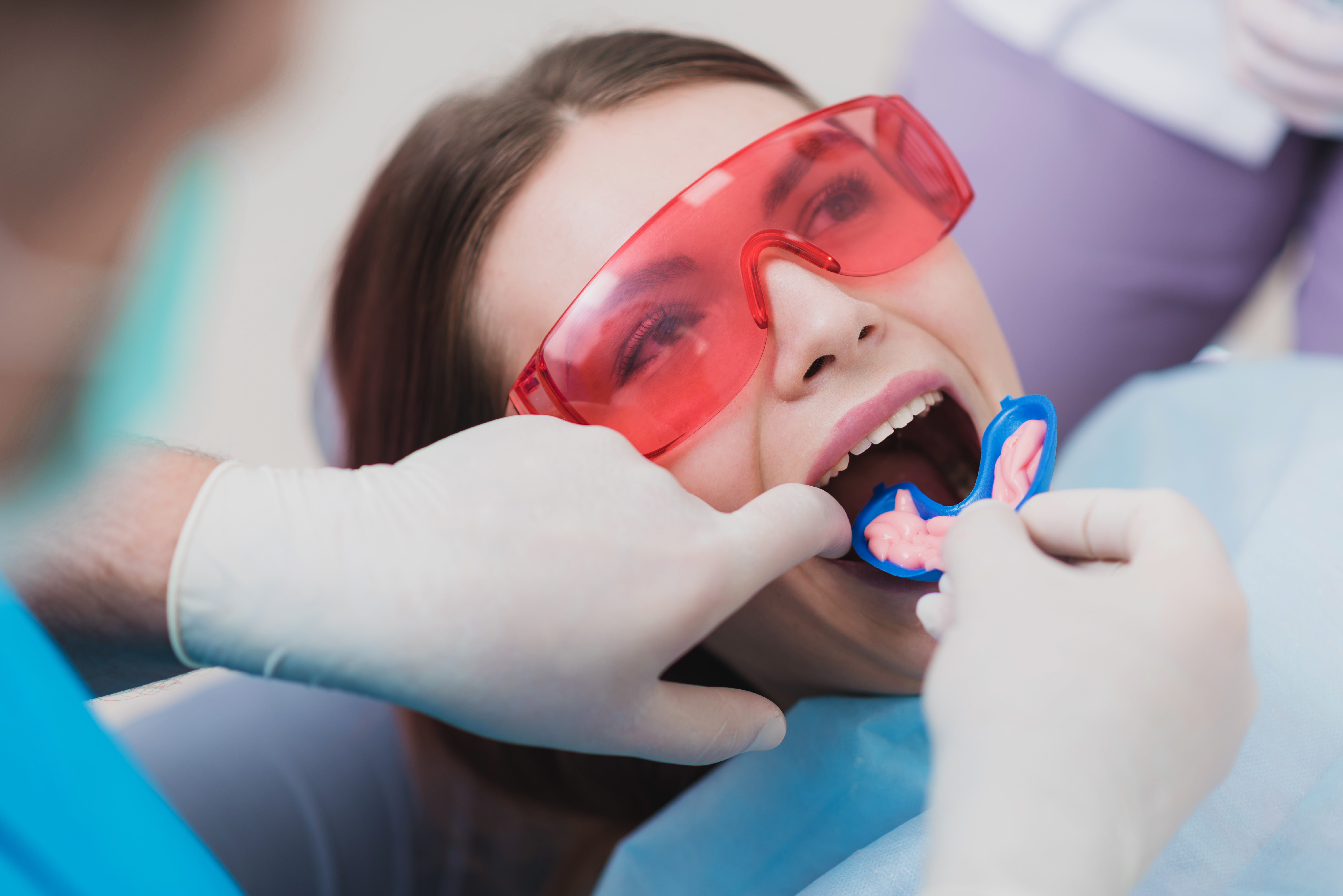dentist putting fluoride tray into a young woman's mouth