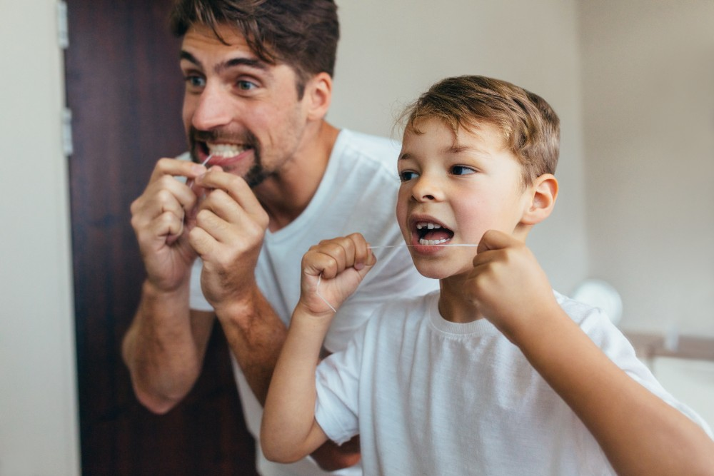 father teaching son how to floss