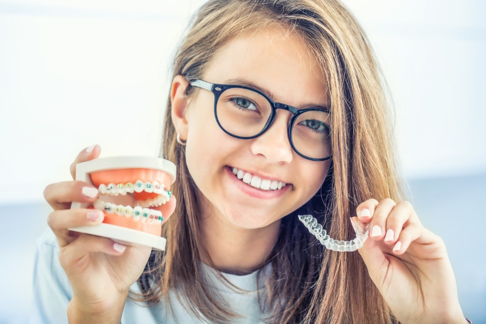 a teenage girl holding up a model of braces in one hand and in the other a top set of invisalign