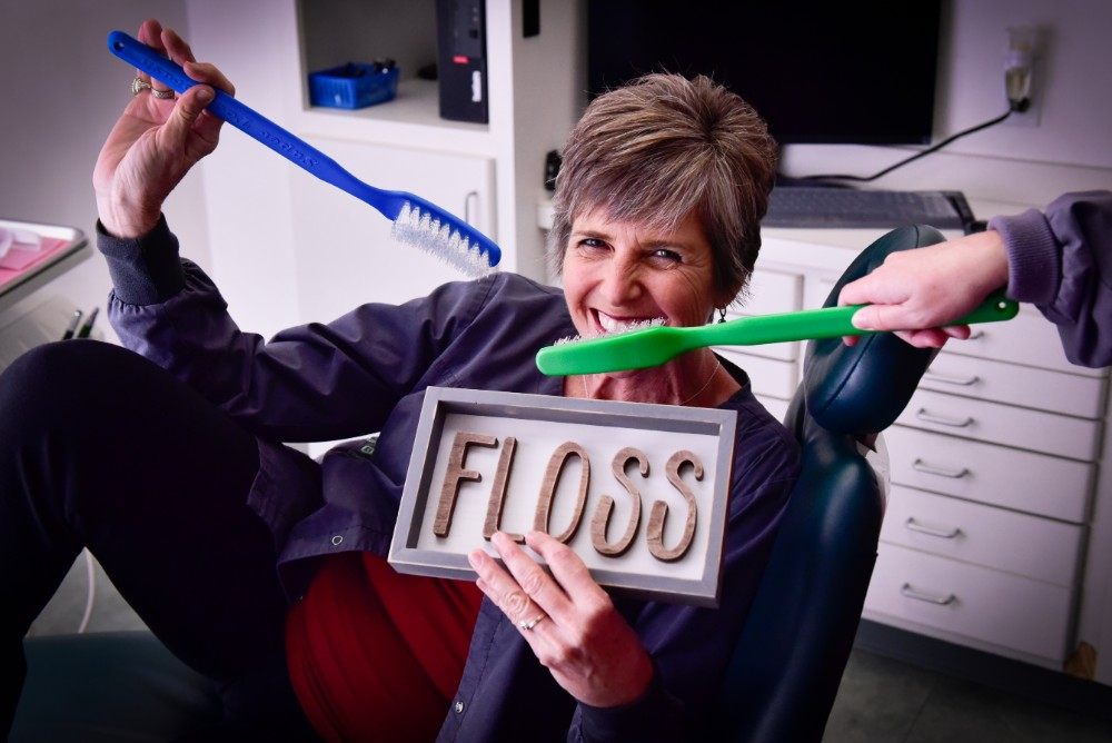 a woman holding giant toothbrush and floss sign