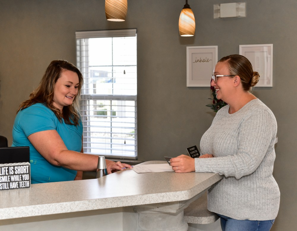 a woman receptionist greeting a patient