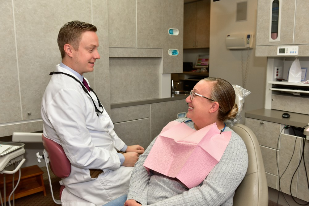 a woman patient smiling as the dentist examines her teeth