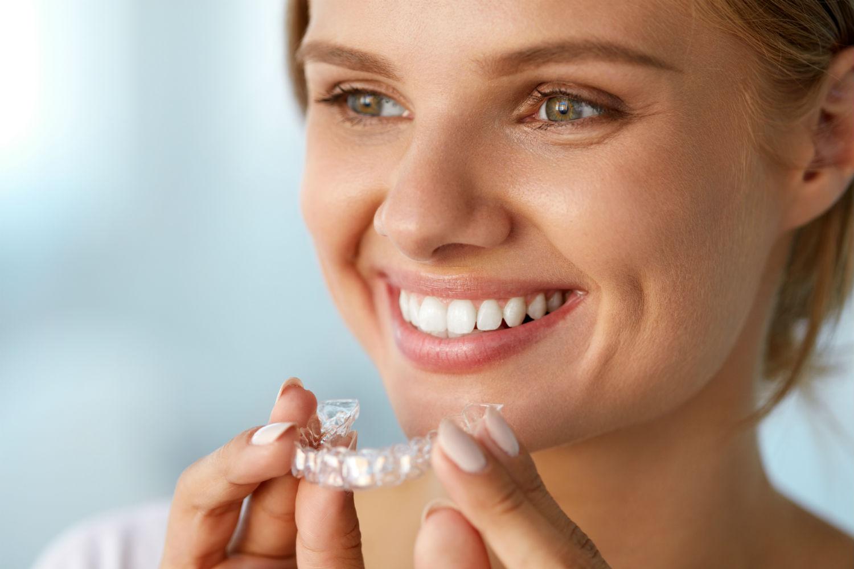 A woman using take-home teeth whitening kits