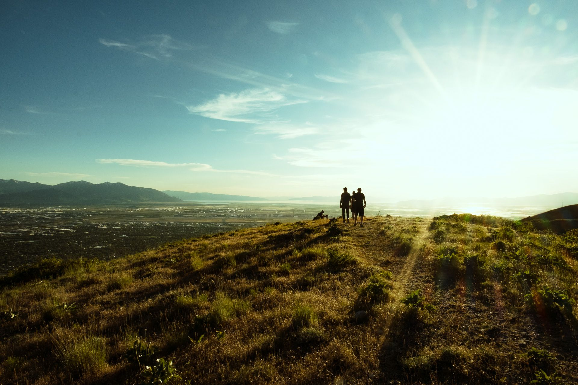 team standing on mountain peak at sunset