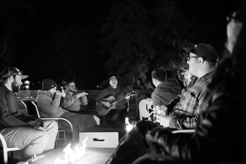 playing music and laughing around fire
